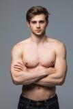 Μυϊκό άτομο αθλητών bodybuilder με έναν γυμνό κορμό σε ένα γκρίζο υπόβαθρο στοκ φωτογραφίες με δικαίωμα ελεύθερης χρήσης