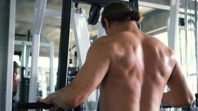 Μυϊκό άτομο γυμνοστήθων που κάνει την καθισμένη άσκηση σειρών καλωδίων στη μηχανή στη γυμναστική φιλμ μικρού μήκους