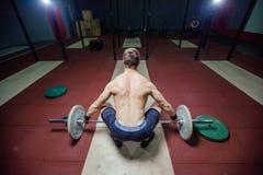Μυϊκό άτομο ικανότητας που προετοιμάζει στο deadlift ένα barbell πέρα από το κεφάλι του στο σύγχρονο κέντρο ικανότητας Λειτουργικ Στοκ φωτογραφίες με δικαίωμα ελεύθερης χρήσης
