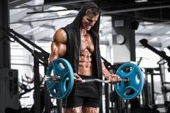 Μυϊκό άτομο που επιλύει στη γυμναστική που κάνει τις ασκήσεις με το barbell για τους δικέφαλους μυς, ισχυρά αρσενικά γυμνά ABS κο στοκ φωτογραφία