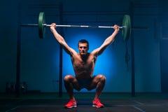 Μυϊκό άτομο που επιλύει με το barbell στη γυμναστική Στοκ Φωτογραφίες