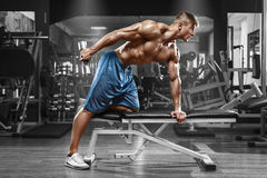 Μυϊκό άτομο που επιλύει στη γυμναστική που κάνει τις ασκήσεις με τους αλτήρες στα triceps, ισχυρά αρσενικά γυμνά ABS κορμών στοκ φωτογραφία
