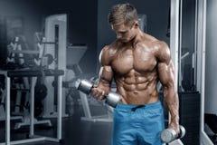 Μυϊκό άτομο που επιλύει στη γυμναστική που κάνει τις ασκήσεις με τους αλτήρες, bodybuilder αρσενικά γυμνά ABS κορμών στοκ εικόνες