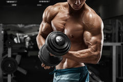 Μυϊκό άτομο που επιλύει στη γυμναστική που κάνει τις ασκήσεις με τους αλτήρες, ισχυρά αρσενικά γυμνά ABS κορμών στοκ εικόνες