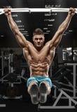 Μυϊκό άτομο που επιλύει στη γυμναστική, που κάνει τις ασκήσεις στομαχιών σε έναν οριζόντιο φραγμό, ισχυρά αρσενικά γυμνά ABS κορμ στοκ εικόνες