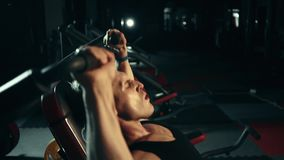 Μυϊκό άτομο που κάνει τις ασκήσεις στους μυς των ώμων, βαρέων βαρών Από την τελευταία δύναμη σκληρά εκπαιδευτικός φιλμ μικρού μήκους