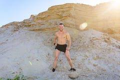 Μυϊκό άτομο στην πρωταρχικής σπουδαιότητας τοποθέτηση επιδέσμων ισχίων σε ένα κλίμα της άμμου Στοκ Εικόνες