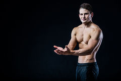 Μυϊκό αθλητικό σημείο ατόμων γυμνοστήθων με δύο χέρια στο κενό copyspace Προκλητικό bodybuilder που παρουσιάζει σώμα του στο Μαύρ στοκ φωτογραφίες