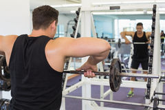 Μυϊκό bodybuilder που ανυψώνει το μεγάλο μαύρο βάρος barbell που κοιτάζει στον καθρέφτη Στοκ Εικόνες