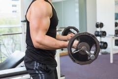 Μυϊκό bodybuilder που ανυψώνει το μεγάλο μαύρο βάρος barbell Στοκ εικόνα με δικαίωμα ελεύθερης χρήσης