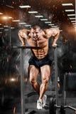 Μυϊκό bodybuilder που επιλύει στη γυμναστική που κάνει τις ασκήσεις σε paral στοκ φωτογραφίες