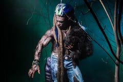 Μυϊκό werewolf με τα dreadlocks με τα μακριά καρφιά μεταξύ του πίτουρου Στοκ Φωτογραφία