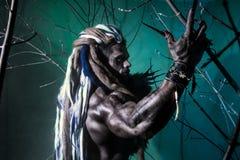 Μυϊκό werewolf πορτρέτου με τα dreadlocks μεταξύ των κλάδων Στοκ Εικόνα