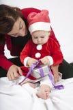 Μωρό Άγιου Βασίλη και mom δώρο ανοίγματος Στοκ Φωτογραφία