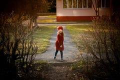 Μωρό 3 έτη με μακρυμάλλη Σε μια κόκκινη beret και παλτών περιστροφή στην οδό, στις ακτίνες του ήλιου Το κράτος στοκ φωτογραφίες
