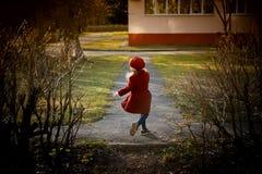 Μωρό 3 έτη με μακρυμάλλη Σε μια κόκκινη beret και παλτών περιστροφή στην οδό, στις ακτίνες του ήλιου Το κράτος στοκ εικόνες με δικαίωμα ελεύθερης χρήσης