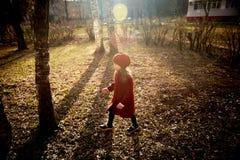 Μωρό 3 έτη με μακρυμάλλη Σε μια κόκκινη beret και παλτών περιστροφή στην οδό, στις ακτίνες του ήλιου Το κράτος στοκ φωτογραφία με δικαίωμα ελεύθερης χρήσης