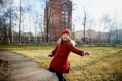 Μωρό 3 έτη με μακρυμάλλη Σε μια κόκκινη beret και παλτών περιστροφή στην οδό, στις ακτίνες του ήλιου Το κράτος στοκ εικόνες