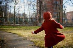 Μωρό 3 έτη με μακρυμάλλη Σε μια κόκκινη beret και παλτών περιστροφή στην οδό, στις ακτίνες του ήλιου Το κράτος στοκ εικόνα με δικαίωμα ελεύθερης χρήσης
