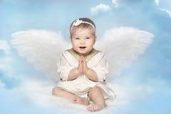 Μωρό αγγέλου με τα φτερά Amur, ευτυχής συνεδρίαση Cupid παιδιών στον ουρανό θαμπάδων στοκ εικόνες