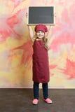 Μωρό, ευτυχές παιδί με τον πίνακα εμβλημάτων στην κουζίνα ή εστιατόριο Στοκ φωτογραφία με δικαίωμα ελεύθερης χρήσης