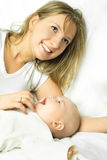 μωρό ευτυχές το λευκό καναπέδων μητέρων της Στοκ Εικόνα