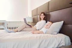 Μωρό και μητέρα με ένα lap-top που λειτουργεί σε ένα κρεβάτι Στοκ Εικόνες