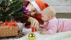 Μωρό και μπαμπάς κάτω από το χριστουγεννιάτικο δέντρο απόθεμα βίντεο