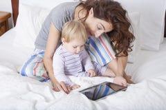 Μωρό και ταμπλέτα μητέρων στο κρεβάτι Στοκ Εικόνες