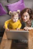 Μωρό και mom εξέταση το lap-top Στοκ Εικόνα