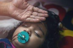 Μωρό κοιμισμένο με τον ειρηνιστή ενώ οι γονείς φροντίζουν στοκ φωτογραφία