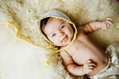 Μωρό με ένα πλεκτό λευκό μωρό καπέλων στην πλάτη Στοκ φωτογραφία με δικαίωμα ελεύθερης χρήσης