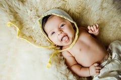 Μωρό με ένα πλεκτό λευκό μωρό καπέλων στην πλάτη Στοκ φωτογραφίες με δικαίωμα ελεύθερης χρήσης