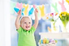 Μωρό με τα αυτιά λαγουδάκι στο κυνήγι αυγών Πάσχας Στοκ Εικόνες