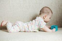 Μωρό με τον κύβο στον καναπέ Στοκ φωτογραφία με δικαίωμα ελεύθερης χρήσης