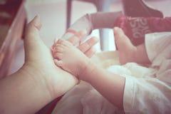 Μωρό ποδιών λαβής χεριών mom, εκλεκτής ποιότητας τόνος Στοκ Εικόνα