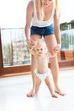 Μωρό που λαμβάνει τα πρώτα μέτρα με τη βοήθεια μητέρων Στοκ Φωτογραφία