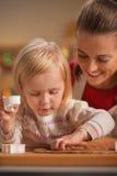 Μωρό που βοηθά άλλα τέμνοντα μπισκότα Χριστουγέννων από τη ζύμη Στοκ Εικόνες