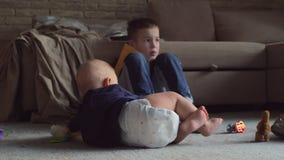 Μωρό που σέρνεται κοντά στον αδελφό απόθεμα βίντεο