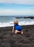 Μωρό που σέρνεται στη μαύρη ηφαιστειακή παραλία άμμου χώρων Λα Playa Στοκ Φωτογραφία