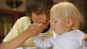 Μωρό που τρώει τα τρόφιμα στο εστιατόριο Ο έφηβος ταΐζει τη νεώτερη αδελφή με ένα κουτάλι του παγωτού για πρώτη φορά Το μωρό φιλμ μικρού μήκους