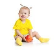 Μωρό που τρώει τη συνεδρίαση μήλων που απομονώνεται στοκ εικόνες