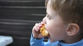 Μωρό που τρώει το τηγανισμένο κοτόπουλο σε ένα εστιατόριο γρήγορου φαγητού, κινηματογράφηση σε πρώτο πλάνο απόθεμα βίντεο