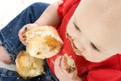 μωρό που τρώει muffins κοριτσιών Στοκ φωτογραφία με δικαίωμα ελεύθερης χρήσης