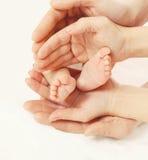 Μωρό ποδιών κινηματογραφήσεων σε πρώτο πλάνο στη μητέρα και τον πατέρα χεριών Στοκ Φωτογραφία