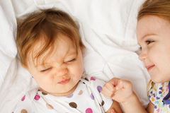 Μωρό στα φύλλα με την αδελφή Στοκ Φωτογραφίες