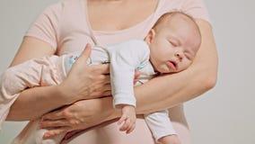 Μωρό στα όπλα μητέρων που πέφτουν κοιμισμένα Στοκ εικόνα με δικαίωμα ελεύθερης χρήσης