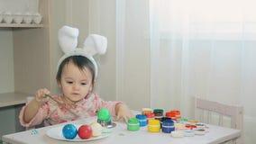 Μωρό στη συνεδρίαση κοστουμιών λαγουδάκι πίσω από έναν άσπρο πίνακα HD 1920x1080 απόθεμα βίντεο