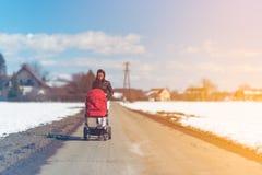 Μωρό στον κόκκινο περιπατητή στην επαρχία τομέων με τη μητέρα Χαλαρώστε στη φύση στη χειμερινή ηλιόλουστη ημέρα στοκ φωτογραφίες