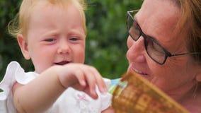 Μωρό στο άσπρο παιχνίδι φορεμάτων με τον ανεμιστήρα καυτό καλοκαίρι ημερών
